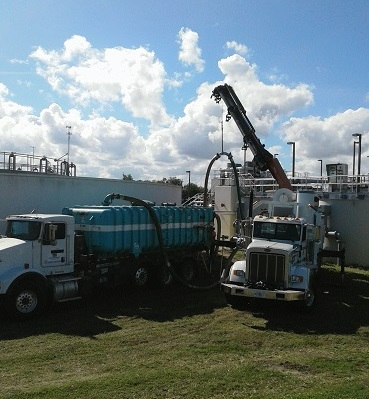 Large white truck with extended boom arm performing grit removal in nearby tank next to large blue roll off truck.