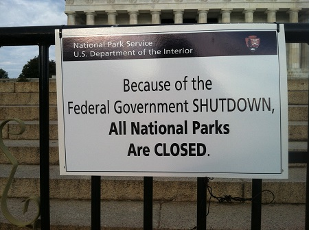 "White sign on black fence posted on front of government property reading ""Because of the federal government shutdown, all national parks are closed."""