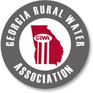 """Georgia Rural Water Association logo.  A gray circle with the words """"Georgia Rural Water Association"""" text around the edges in white, and a red state of Georgia depicted in the center."""