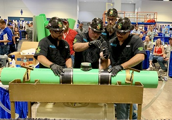 Tallahassee's Sludge Soldiers performing the Ops Challenge Collections event; 4 team members in black shirts and black hardhats bent over a bright green pipe.