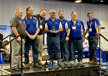 Polk County's Biowizards getting 5th place trophy at the Ops Challenge awards ceremony; 5 team members in matching blue shits lined up on stage.