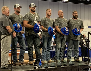 "JEA's team, Fecal Matters lined up on the Ops Challenge awards ceremony stage; 5 team members in a row, holding shiny blue hardhats in front with their logo onthe front, ""JEA."""