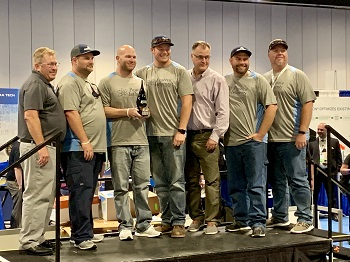 Team Positive Influents from Destin at the Ops Challenge awards ceremony posing with 1st place trophy; 5 team members in matching gray shirts lined up on stage.