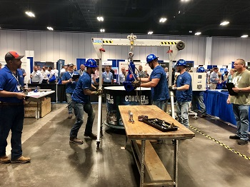 JEA's Fecal Matters team during the Ops Challenge Maintenance event challenge; 3 team members in blue shirts and shiny blue matching hardhats moving a large contraption.
