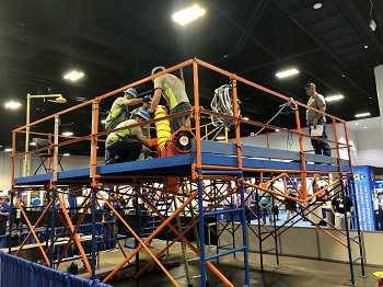 Destin's team Positive Influents during the Ops Challenge Safety event; 3 team members in gray shirts and blue hardhats getting ready to begin with 4th team member looking on from the right side.