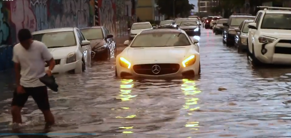 Cars stranded in the middle of a flooded street in Miami-Dade, Florida.