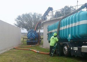 Combination3® Truck with extended boom at work removing sand and grit from Central FL facility.